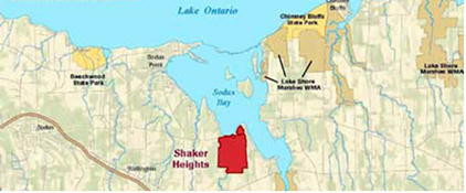 A map which features the parcel of land which was acquired by the Department of Environmental Conservation, highlighted in red. From the map, you can tell that the newly acquired land is located along the shore of Lake Ontario, but more specifically, within Sodus Bay.
